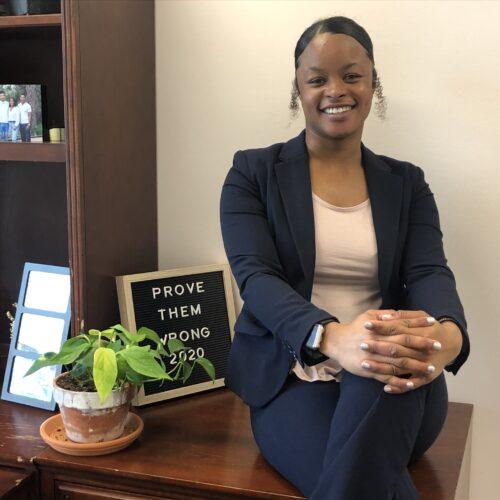 Aspen Davis Black woman sitting on desk of Atlas Consulting Group office - hands folded